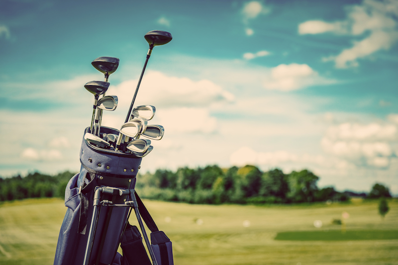 bigstock-Golf-equipment-bag-standing-on-224213497