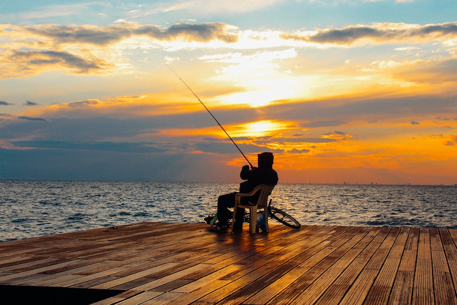 man fishing in ocean sunset
