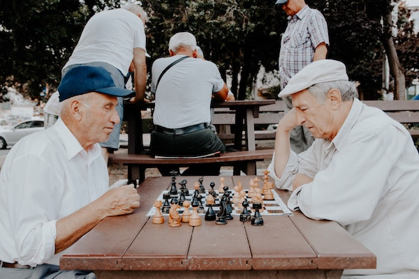 two senior men playing chess together